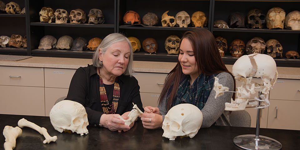 Student and professor examining skull.